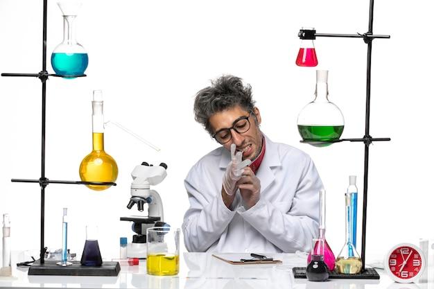 Vorderansicht chemiker mittleren alters im weißen medizinischen anzug, der mit lösungen sitzt