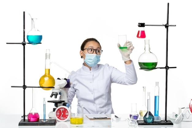 Vorderansicht chemikerin im medizinischen anzug mit maske, die verschiedene lösungen auf hellweißem hintergrund-spritzvirus-chemielabor hält
