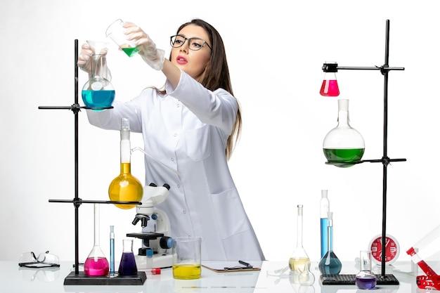 Vorderansicht chemikerin im sterilen medizinischen anzug, die mit lösungen auf der weißen hintergrundlaborvirus-covid-pandemie-wissenschaft arbeitet