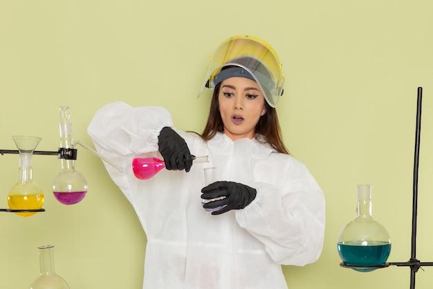 Vorderansicht chemikerin in speziellem schutzanzug, der mit lösungen auf der hellgrünen oberfläche arbeitet