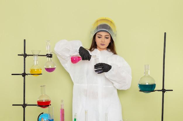 Vorderansicht chemikerin in speziellem schutzanzug, der mit verschiedenen lösungen auf der grünen oberfläche arbeitet