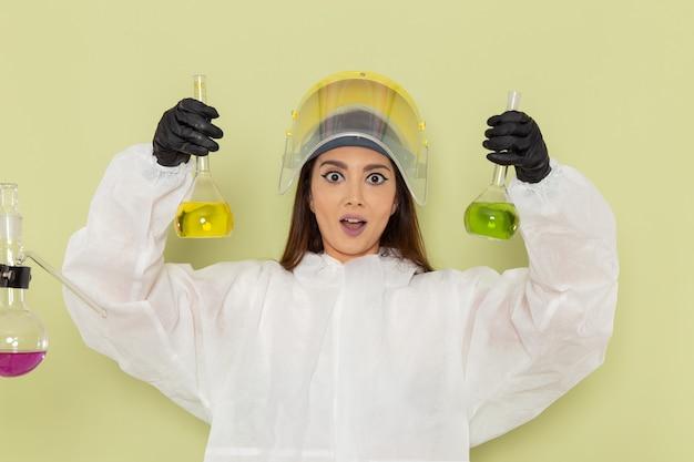 Vorderansicht chemikerin in speziellem schutzanzug mit verschiedenen lösungen auf grüner oberfläche