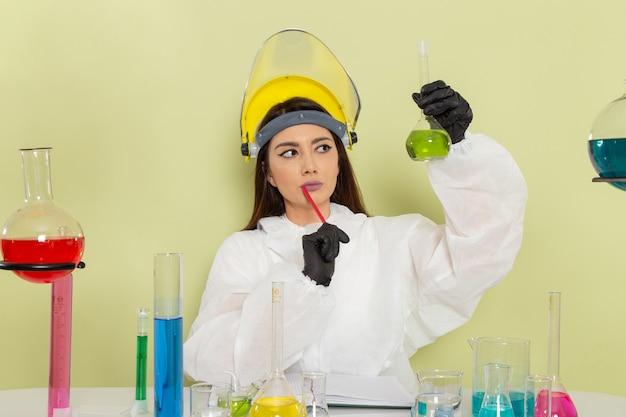 Vorderansicht chemikerin in speziellem schutzanzug vor dem tisch mit lösungen, die mit ihnen auf grüner oberfläche arbeiten