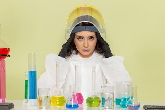Vorderansicht chemikerin in speziellem schutzanzug vor tisch mit lösungen mit kopfschmerzen auf grüner oberfläche