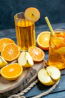 Vorderansicht cocktail geschnittene orangen und äpfel auf holzbrett auf dunkel