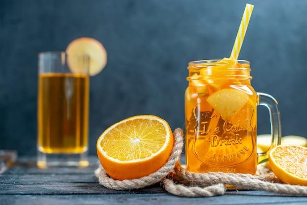 Vorderansicht cocktail geschnittene orangen und äpfel auf holzbrett auf dunklem, isoliertem hintergrund