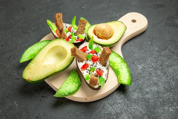 Vorderansicht cremige avocados mit brot und pfeffer und frischen avocados auf der grauzone