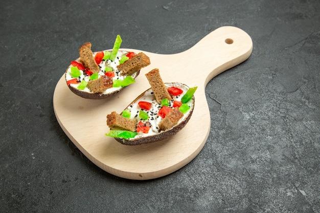 Vorderansicht cremige avocados mit geschnittenen paprika und brotstücken auf grauzone