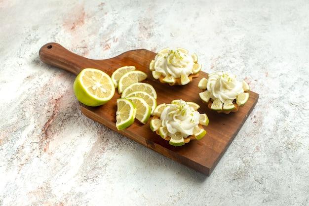 Vorderansicht cremige köstliche kuchen mit zitronenscheiben auf weißem oberflächenkuchenkeksplätzchen süßer sahnetee
