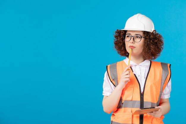 Vorderansicht denkende weibliche baumeisterin in uniform und helm auf blauer wand