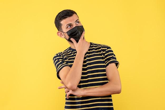 Vorderansicht denkender junger mann im gelb-weiß gestreiften gelben hintergrund des gestreiften t-shirts