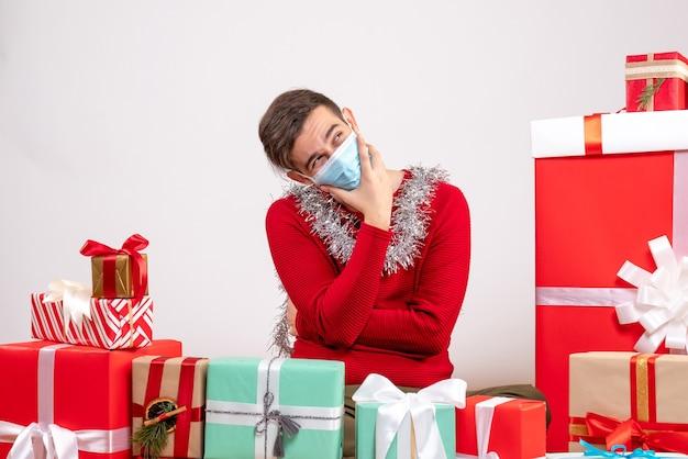 Vorderansicht denkender junger mann mit maske, die um weihnachtsgeschenke sitzt