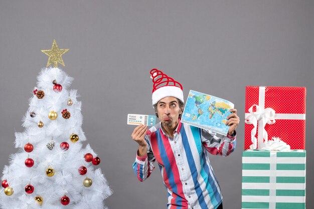 Vorderansicht denkender mann mit spiralfeder-weihnachtsmannhut, die weltkarte und reiseticket hält
