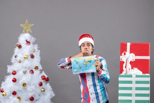 Vorderansicht denkender mann mit spiralfeder-weihnachtsmütze, die weltkarte hält