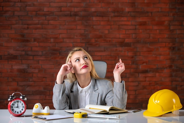 Vorderansicht denkender weiblicher ingenieur, der im büro sitzt