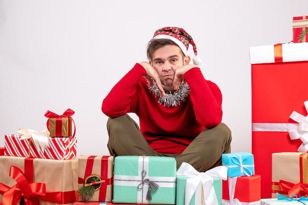 Vorderansicht deprimierte jungen mann, der um weihnachtsgeschenke sitzt