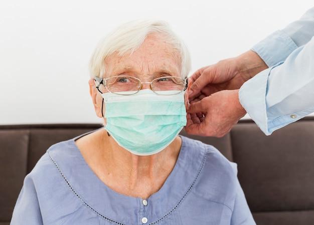 Vorderansicht der älteren frau, die auf medizinische maske versucht