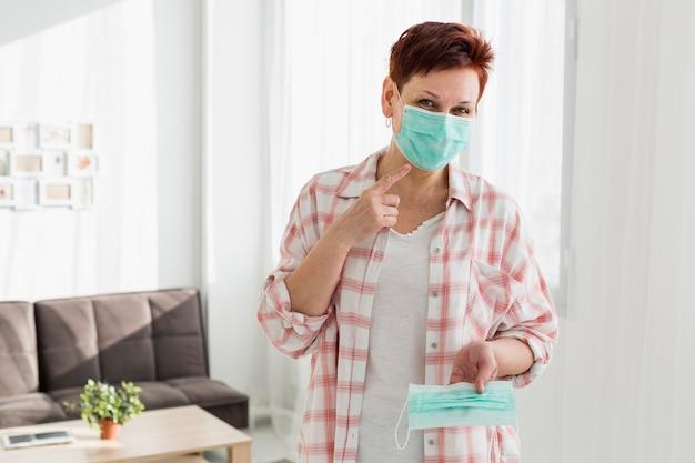 Vorderansicht der älteren frau, die auf medizinische maske zeigt, die sie trägt