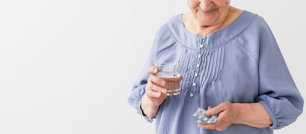 Vorderansicht der älteren frau, die ihre pillen mit kopienraum nimmt