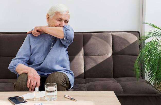 Vorderansicht der älteren frau, die in ihrem ellbogen hustet