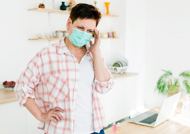 Vorderansicht der älteren frau, die medizinische maske trägt und sich nicht gut fühlt