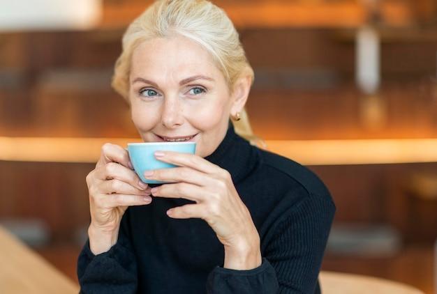 Vorderansicht der älteren frau, die tasse kaffee während der arbeit trinkt