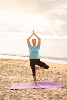 Vorderansicht der älteren frau, die yoga am strand praktiziert