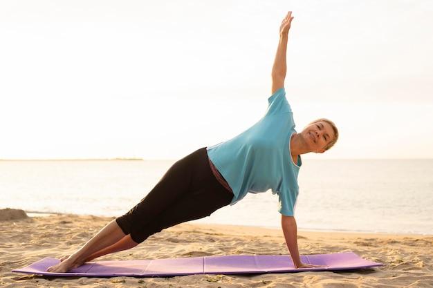 Vorderansicht der älteren frau, die yoga am strand tut