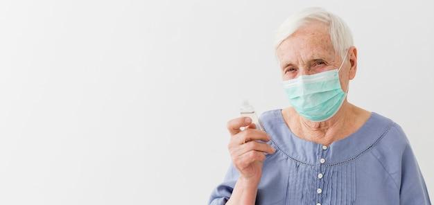 Vorderansicht der älteren frau mit der medizinischen maske, die händedesinfektionsmittel hält