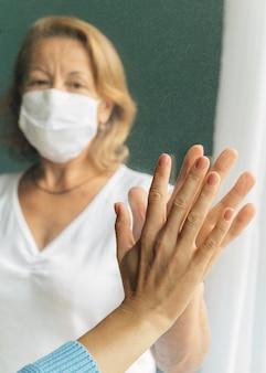 Vorderansicht der älteren frau mit der medizinischen maske, die hand mit jemandem durch fenster berührt