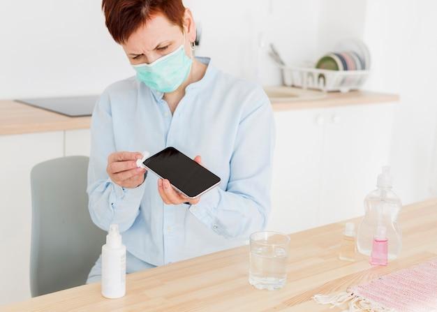Vorderansicht der älteren frau mit der medizinischen maske, die ihr smartphone zu hause desinfiziert