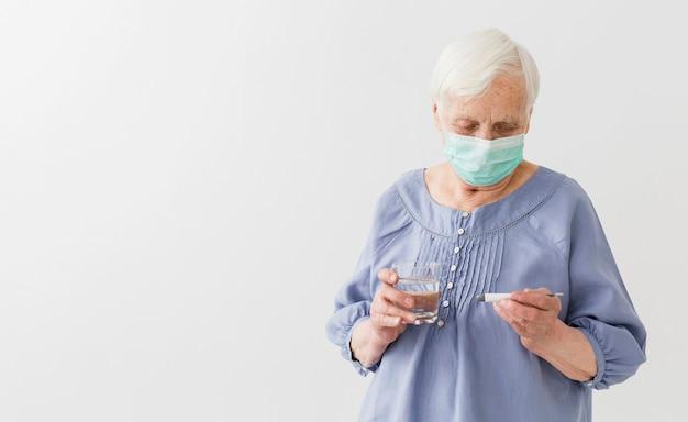 Vorderansicht der älteren frau mit der medizinischen maske, die thermometer mit kopienraum hält