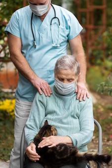 Vorderansicht der älteren frau mit der medizinischen maske und der katze, die von einer männlichen krankenschwester gepflegt werden