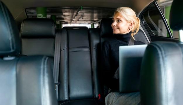 Vorderansicht der älteren geschäftsfrau des smileys, die am laptop im auto arbeitet