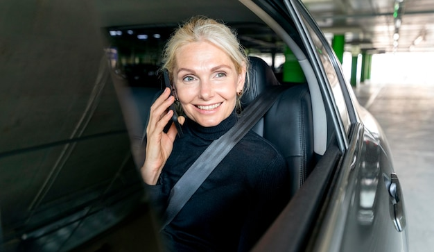 Vorderansicht der älteren geschäftsfrau des smileys, die das telefon im auto spricht