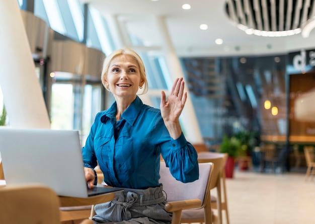 Vorderansicht der älteren geschäftsfrau des smileys, die während der arbeit am laptop nach der rechnung fragt