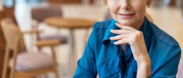 Vorderansicht der älteren geschäftsfrau, die an einem diner aufwirft