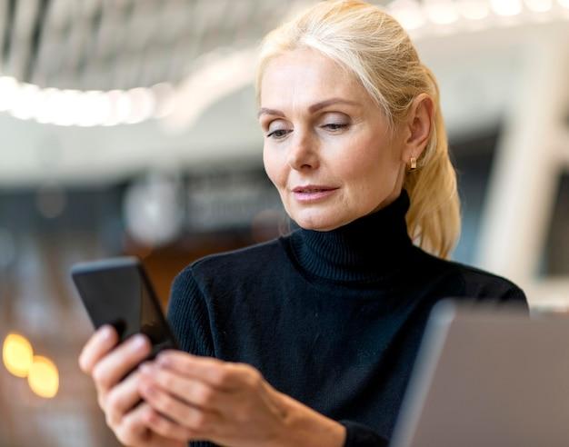 Vorderansicht der älteren geschäftsfrau, die an laptop und smartphone arbeitet