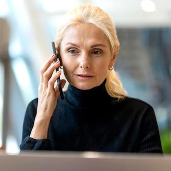 Vorderansicht der älteren geschäftsfrau, die auf smartphone spricht