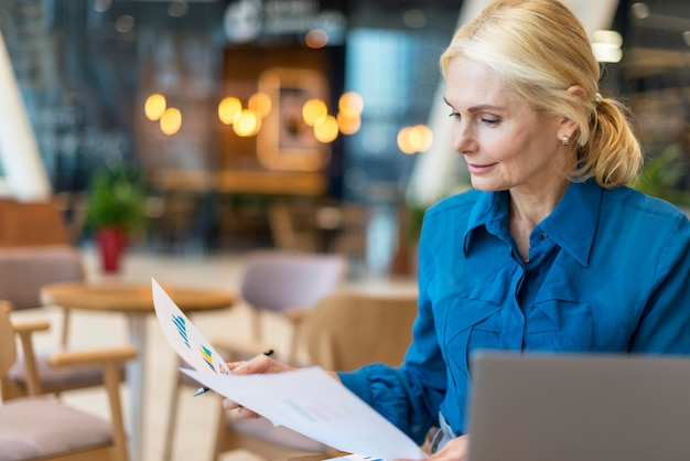 Vorderansicht der älteren geschäftsfrau, die mit papieren und laptop arbeitet