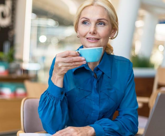 Vorderansicht der älteren geschäftsfrau, die tasse kaffee während der arbeit genießt