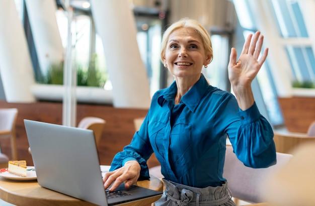 Vorderansicht der älteren geschäftsfrau, die während der arbeit am laptop nach der rechnung fragt