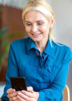Vorderansicht der älteren smiley-frau, die smartphone während der arbeit hält