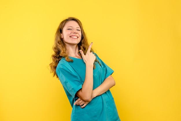 Vorderansicht der ärztin, die auf gelber wand lächelt