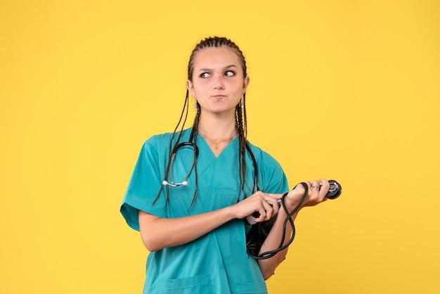 Vorderansicht der ärztin im medizinischen anzug, die ihren druck auf gelbe wand prüft