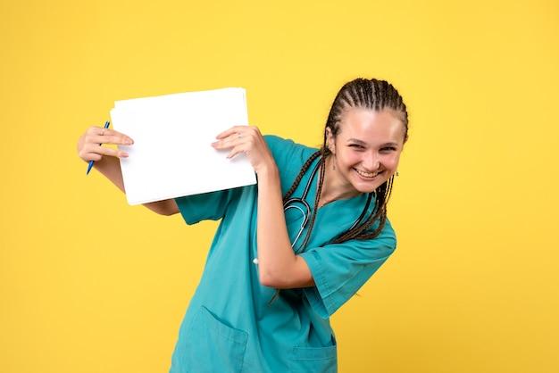Vorderansicht der ärztin im medizinischen anzug, die papiere auf gelber wand hält