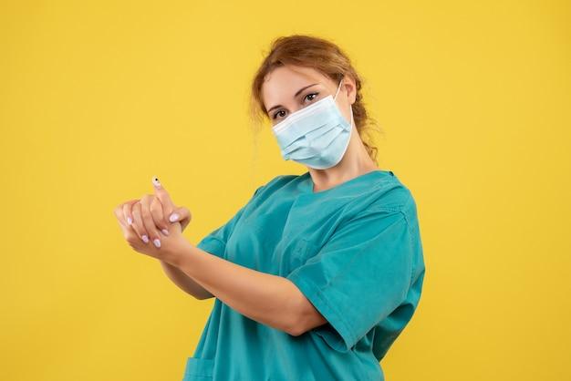 Vorderansicht der ärztin im medizinischen anzug und in der maske auf gelber wand