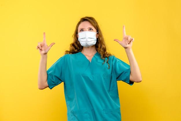 Vorderansicht der ärztin in der maske auf gelber bodenmedizinergesundheits-covid-pandemie