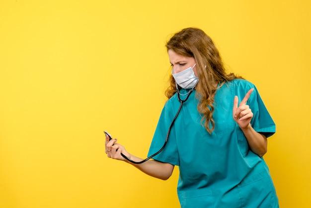 Vorderansicht der ärztin in der maske unter verwendung des stethoskops auf gelber wand