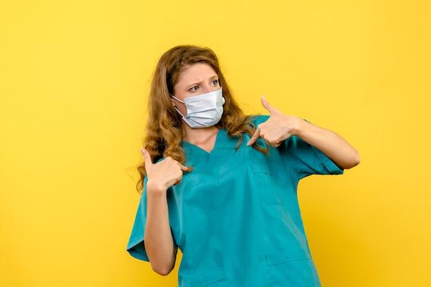 Vorderansicht der ärztin in der sterilen maske auf gelber wand